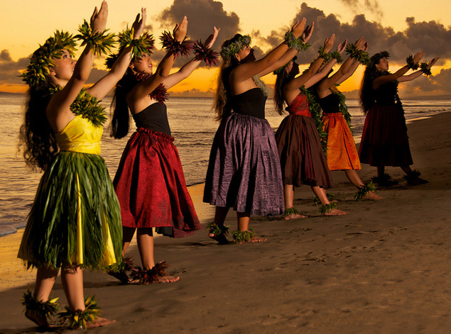 hula dancers performing on the beach in Hawaii at sunset