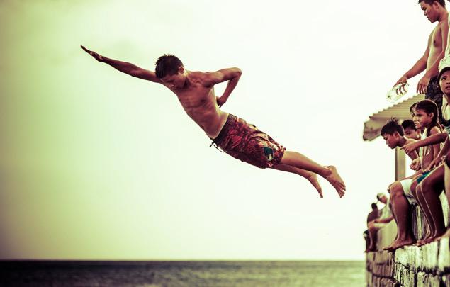 Hawaiian kids jumping off the wall into the ocean