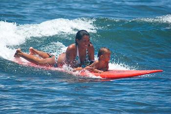 baby and mama surfing at Launiupoko